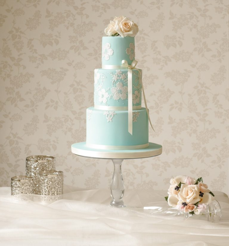 teal wedding cake with lace applique flowers and hand piping