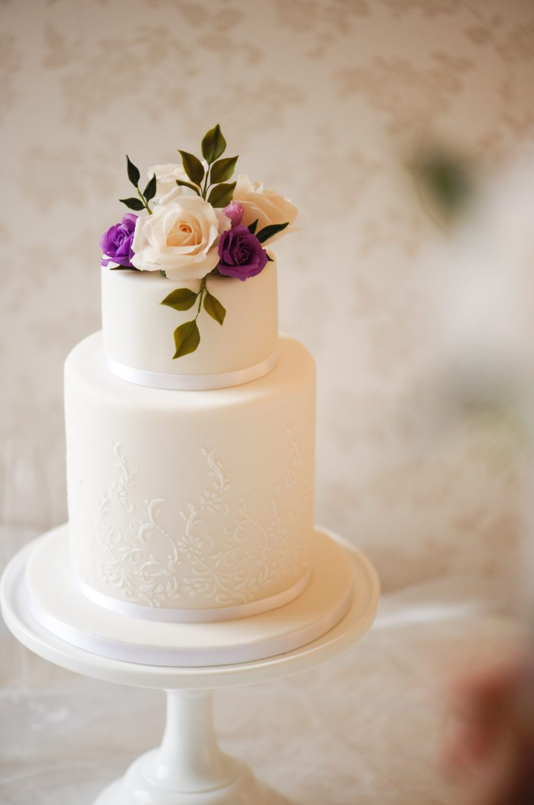 two tier white wedding cakes with purple roses