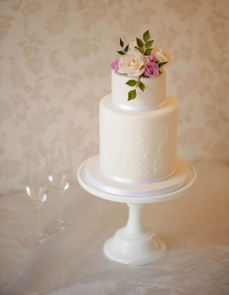 two tier white wedding cake with lavender roses