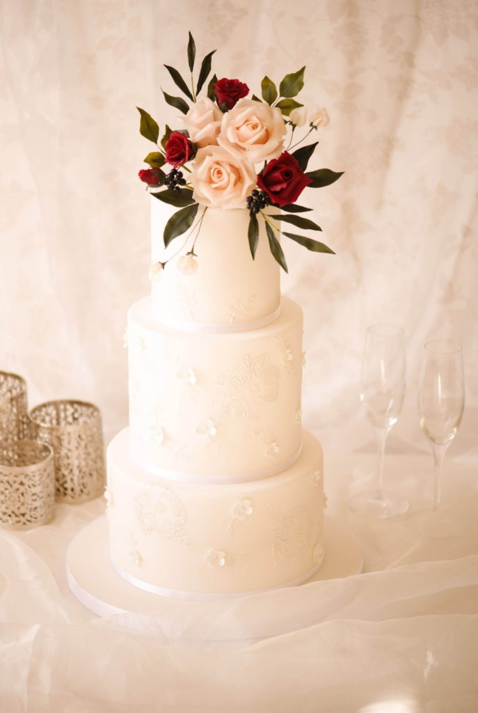 Autumnal white wedding cake with red roses and foliage