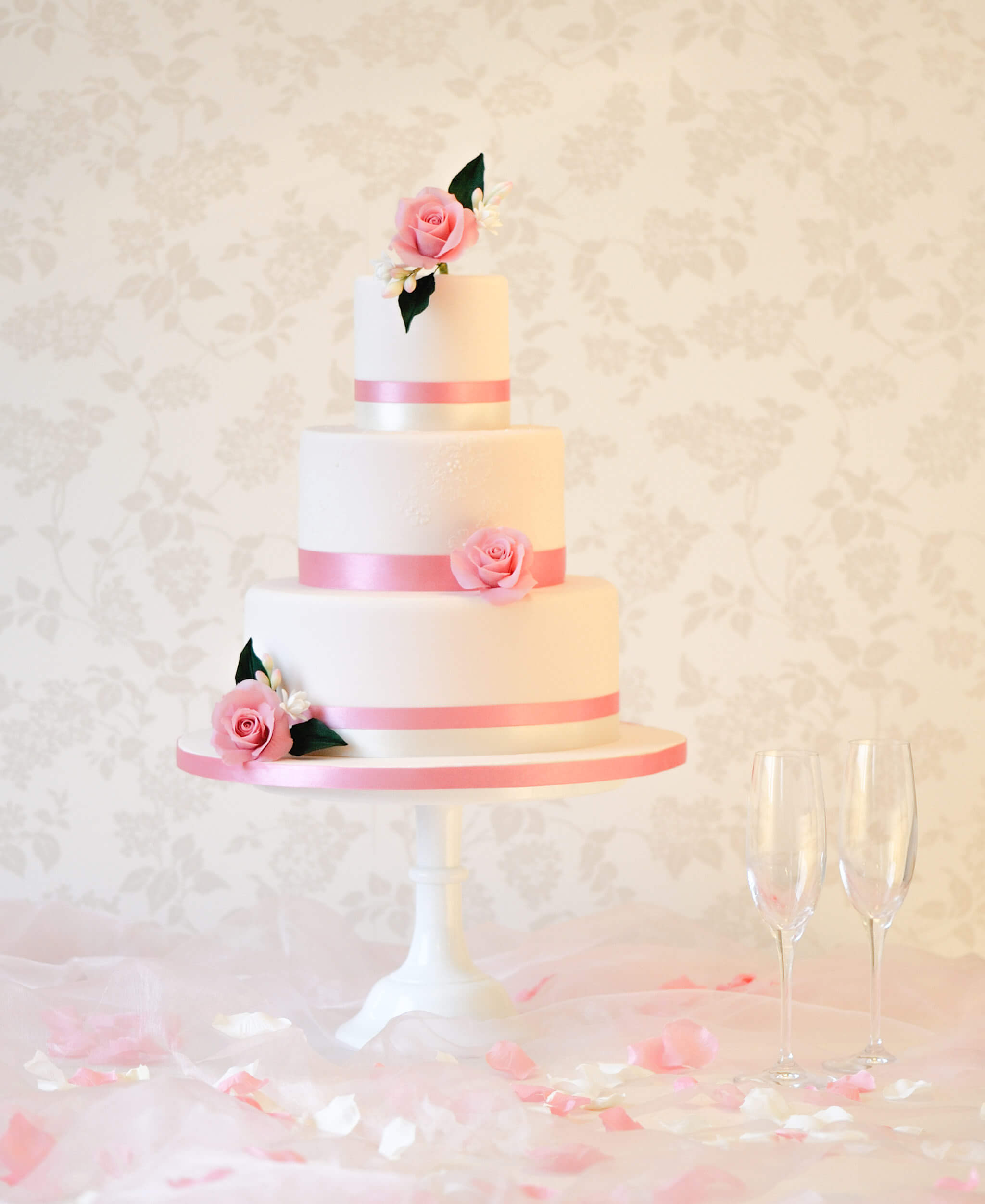 classic wedding cake with pink ribbons