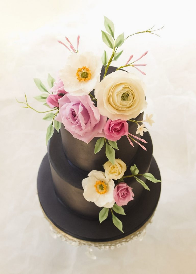 two tier navy wedding cake with handmade summer floral arrangement