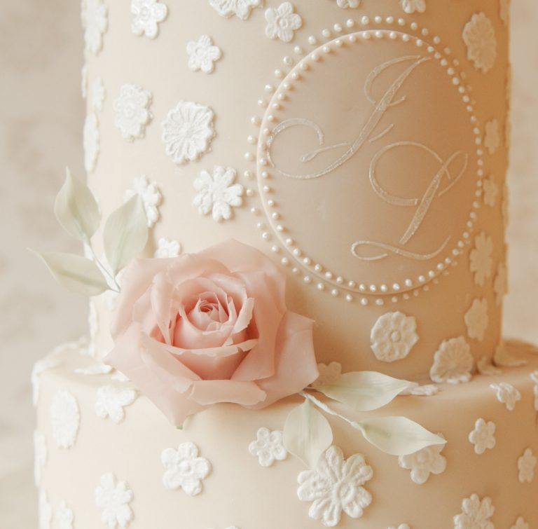 bespoke wedding cakes in aylesbury ivory lace wedding cake with custom monogram and pink rose with white leaves
