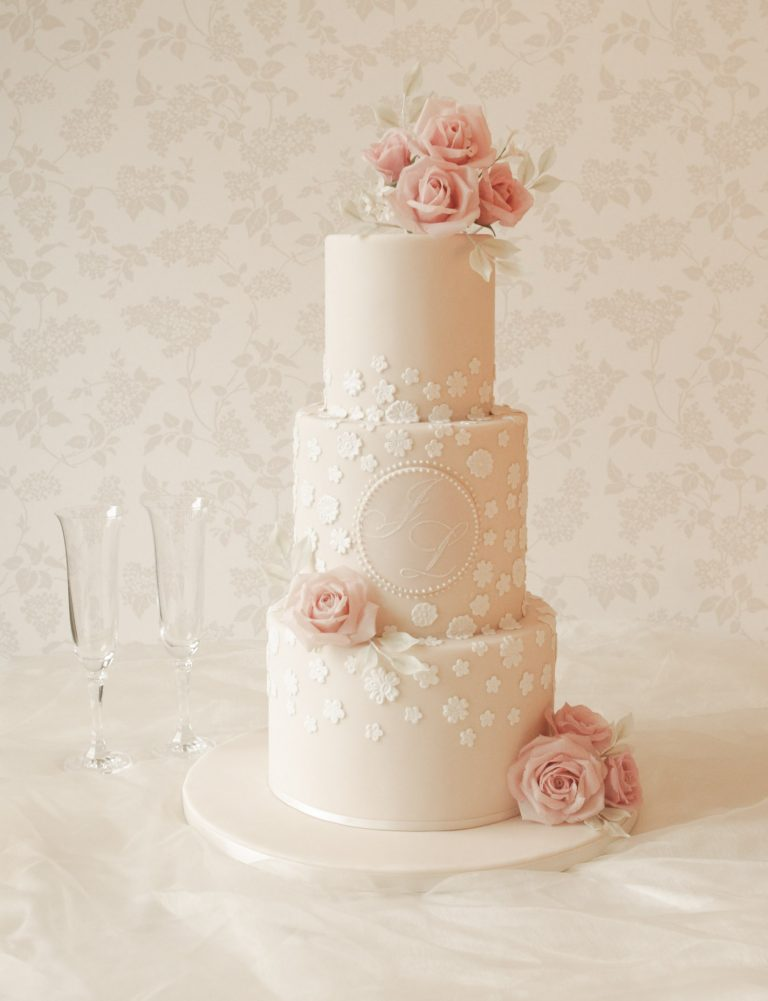 ivory lace wedding cake with custom monogram and pink roses