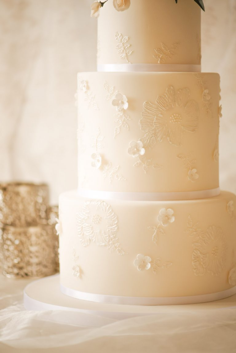 bespoke white wedding cake with hand piped lace flowers and blossoms