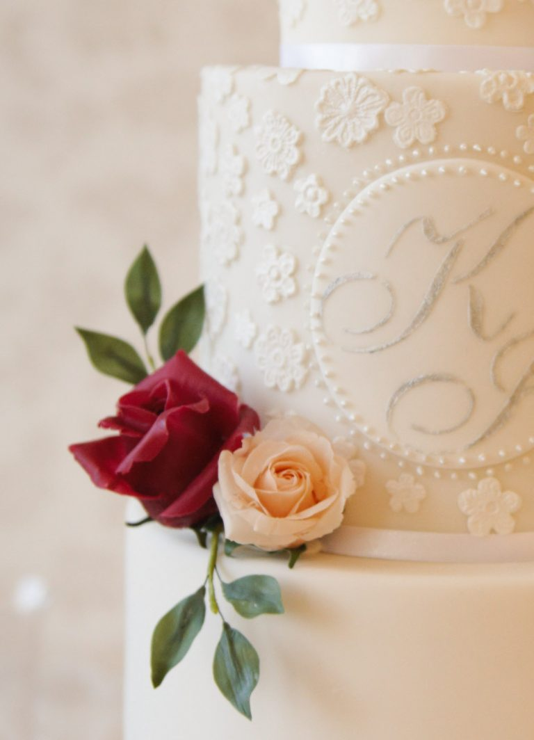 white wedding cake with red and peach rose and custom monogram