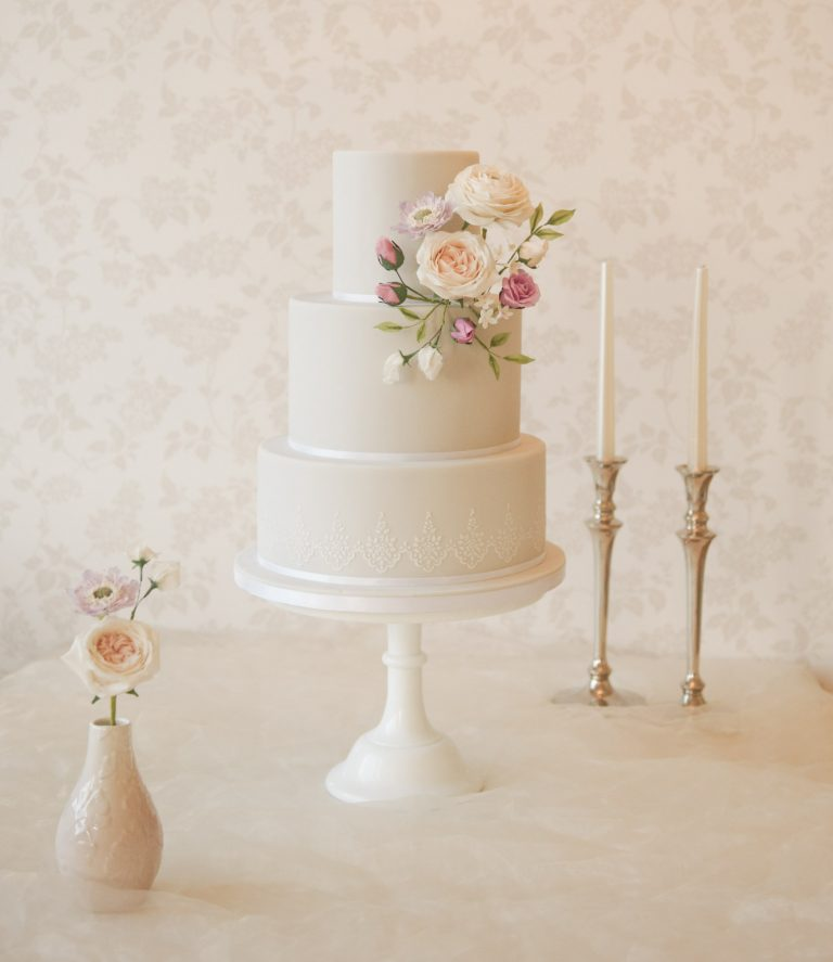pale grey romantic wedding cakes with handmade flowers and white stencilled pattern