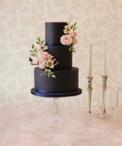 navy wedding cake with pale pink flowers
