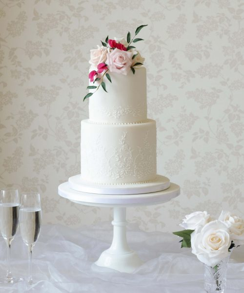 two tier white cake with stencilled pattern and pink and white roses