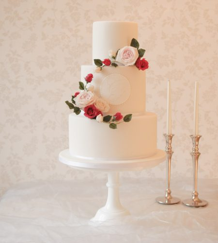 white wedding cake with red and white rose wreath