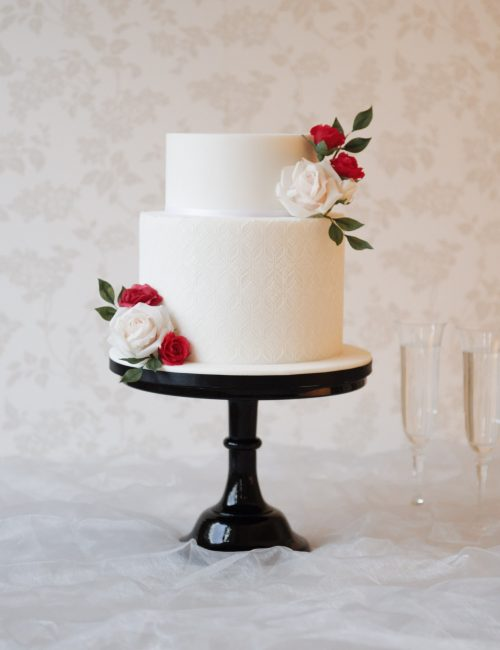 elegant white wedding cake in milton keynes with red and white roses on black cake stand