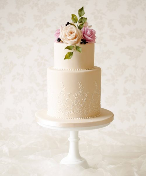 ivory wedding cake with flowers in dusky tones and stencilled pattern on base tier