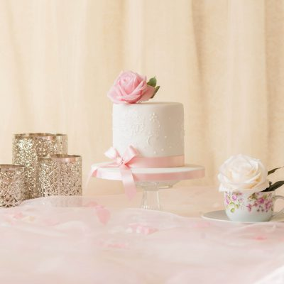 white celebration cake with pearls and rose