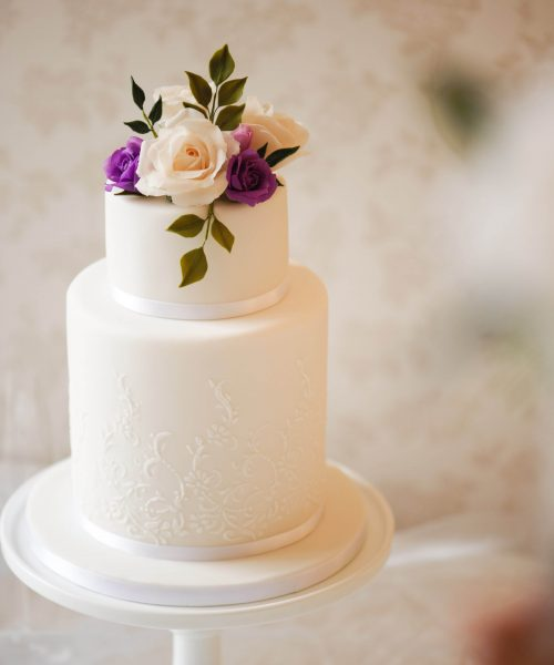 white wedding cake with cream and purple roses